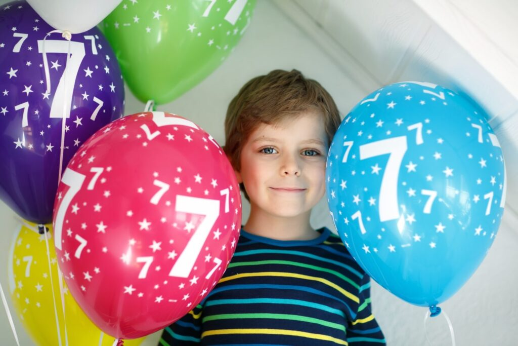 Portrait of happy kid boy with bunch on colorful air balloons on 7 birthday. Smiling school child having fun, celebrating seventh birth day. Family and best friend party